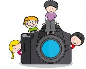 Children peeking from behind--and sitting on--a camera